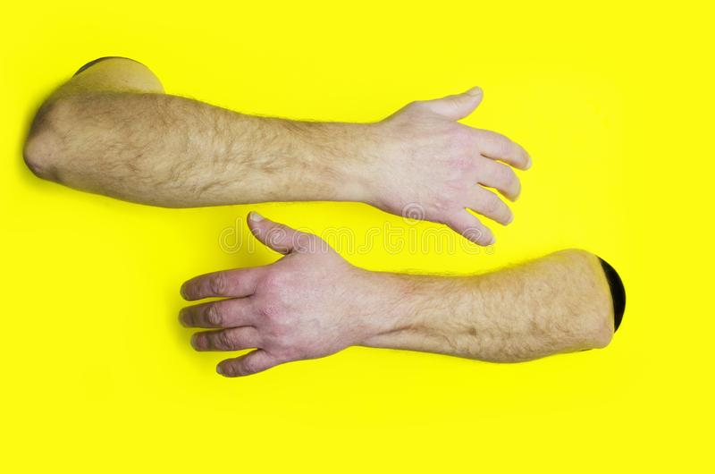 Omhels of koesterend ontwerpsjabloon Mannelijke handen die somebody koesteren tegen gele achtergrond Concept steun royalty-vrije stock foto's