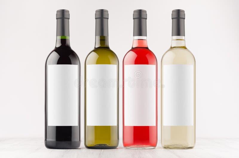 Omhoog bespotten de de inzamelings verschillende kleuren van wijnflessen met witte lege etiketten op witte houten raad, royalty-vrije stock afbeeldingen