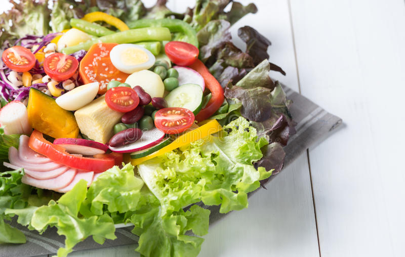 Omhoog gesloten van de verse salade van de mengelingsvegetatie op wit hout royalty-vrije stock afbeelding