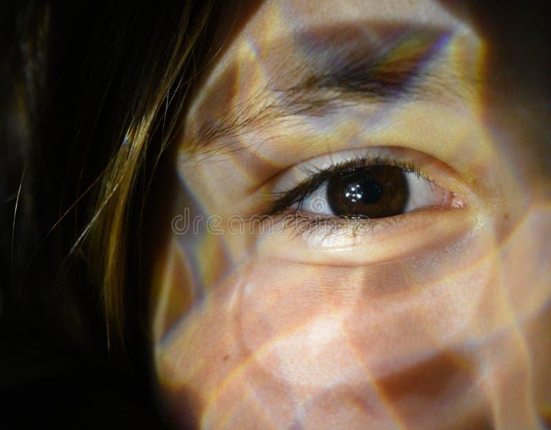 Omhoog gesloten van een vrouwenoog met lichteffect voor haar gezicht royalty-vrije stock foto's