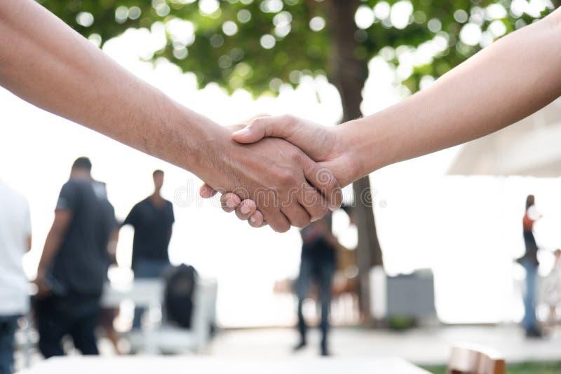 Omhoog gesloten van handschok met mensen op achtergrond Samenwerking tussen bedrijven en Eenheidsconcept Zaken en in openlucht th royalty-vrije stock foto's