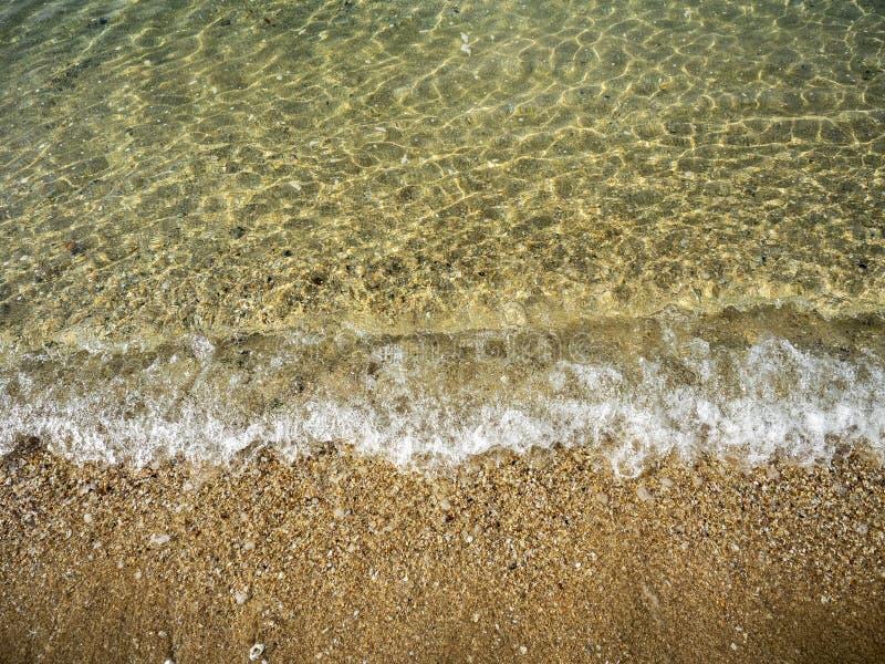 Omhoog gesloten van overzeese golf die zich op het zandstrand bewegen stock fotografie