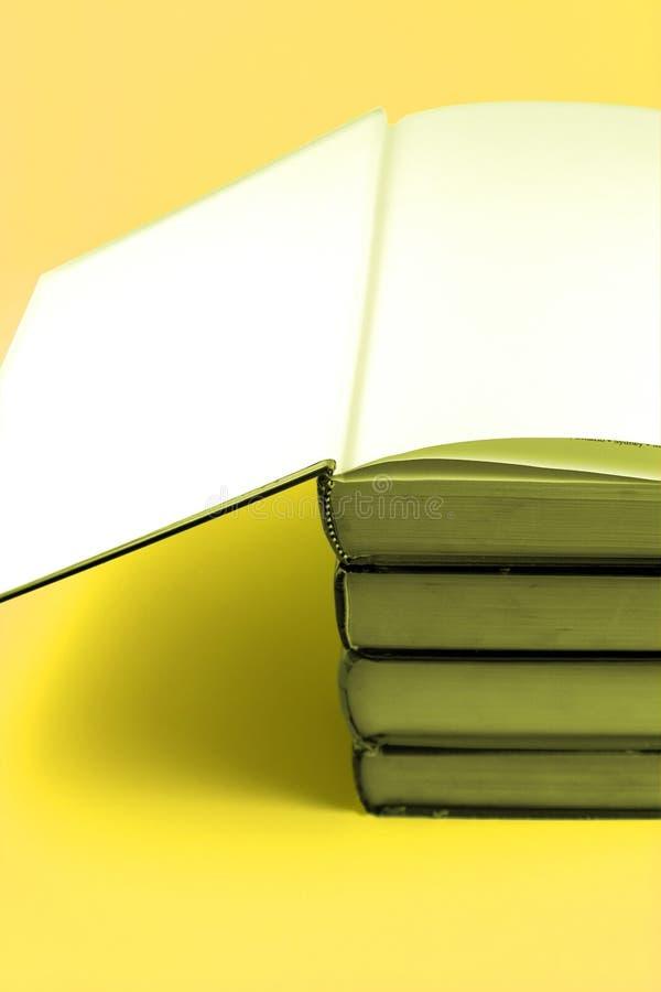 Omhoog Gestapelde boeken - Gele Achtergrond stock afbeeldingen