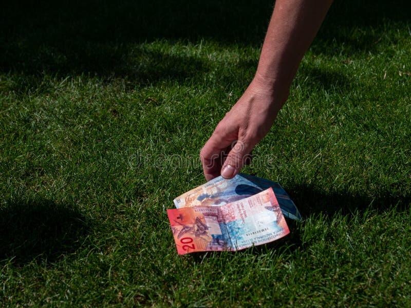 Omhoog het met de hand plukken van geld van de grond Zwitserse munt grasgrond royalty-vrije stock foto