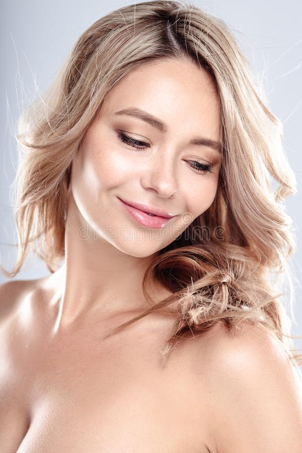Omhoog maakt de blonde jonge vrouw met gezond krullend haar en natuurlijk Mooi modelmeisje met golvend kapsel stock foto