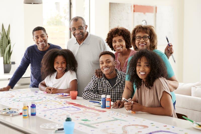 Omhoog sluit de drie generatie Afrikaanse Amerikaanse familie die een teken voor verrassingspartij maken die aan camera glimlache royalty-vrije stock afbeeldingen