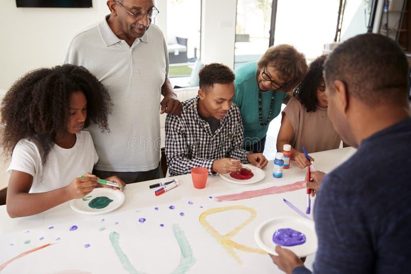 Omhoog sluit de drie generatie Afrikaanse Amerikaanse familie die een teken voor een verrassingspartij samen maken thuis, royalty-vrije stock afbeeldingen