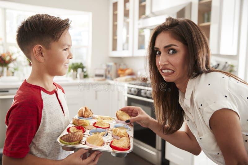 Omhoog sluit de pre-tiener Spaanse jongen die de cakes voorstellen die hij aan zijn teleurgestelde moeder heeft gebakken, royalty-vrije stock foto's