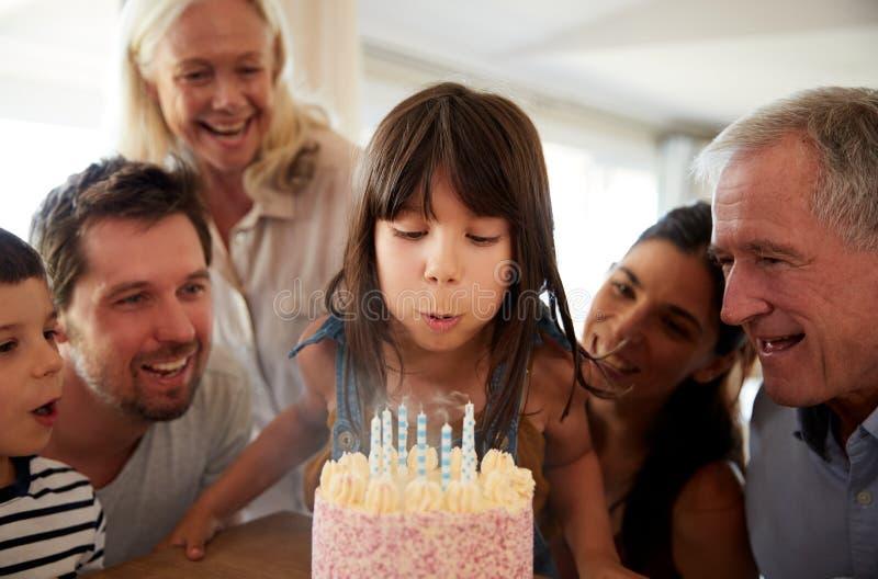 Omhoog sluit het zes éénjarigen witte meisje die die uit de kaarsen op verjaardagscake door haar familie wordt gelet blazen op, royalty-vrije stock foto's