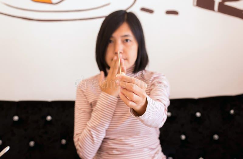 Omhoog sluiten de handen Aziatische vrouwen die tandenstoker houten na maaltijd gebruiken, stock foto
