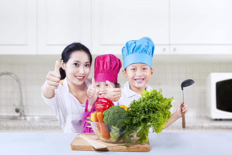 Omhoog thuis geven het de chef-kok vegetarische jonge geitjes en mamma duimen royalty-vrije stock afbeeldingen