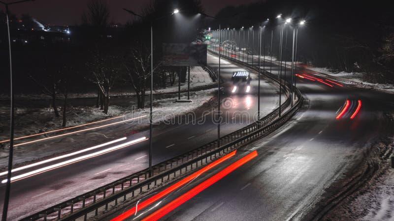 Γρήγορα κινούμενη κυκλοφορία τη νύχτα χειμερινή εποχή έννοια του δρόμου, της αφαίρεσης χιονιού και πάγου, του κινδύνου και της ασ στοκ φωτογραφίες