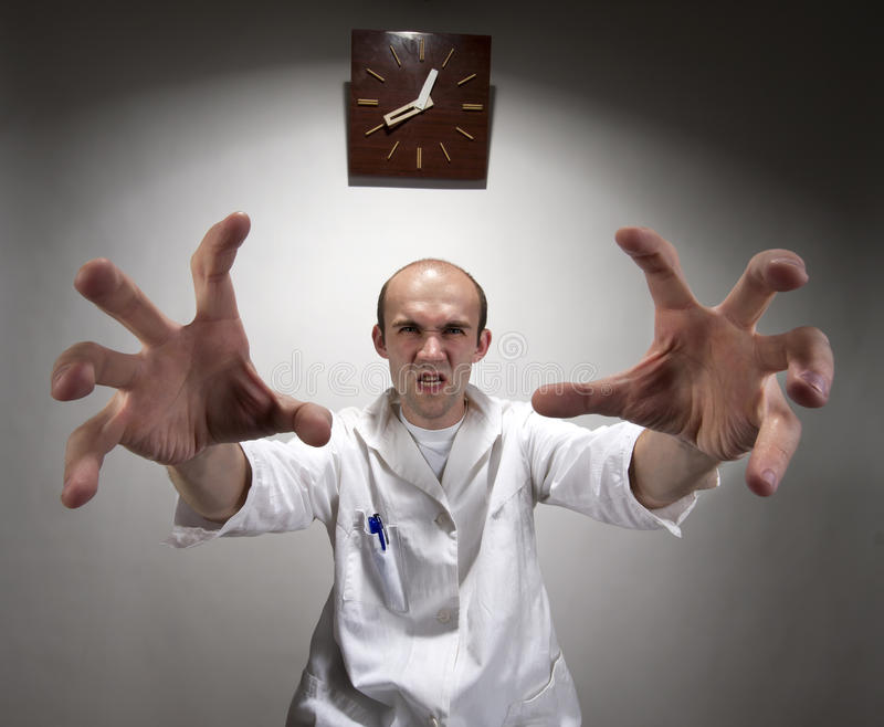 Ominous angry doctor. Reaching his long hands royalty free stock photography