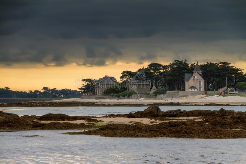 Ominous clouds at the coast in France. Ominous clouds over some beautiful houses at the coast of the Loire-Atlantique in France on a summer sunset in July royalty free stock photography