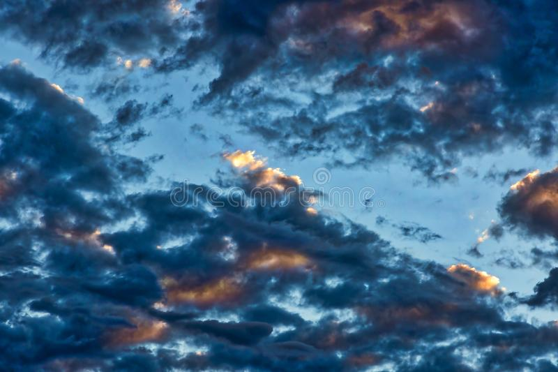 Ominous Clouds with color bursts giving way to a sunny day. Ominous morning clouds giving way to sunny skies stock image