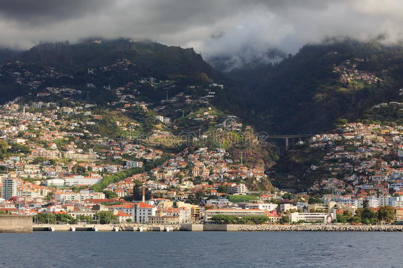 Ominous clouds Funchal. Beautiful cityscape view of the city Funchal, Madeira, seen from the Atlantic ocean, with ominous clouds royalty free stock photos