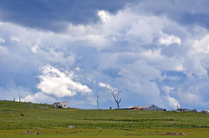 Ominous dramatic storm clouds over farmland. Ominous storm clouds approaching over rolling green hills and farmland in the New South Wales countryside, Australia royalty free stock photography
