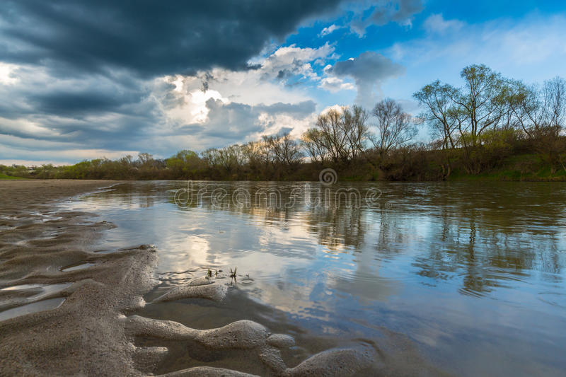 Ominous stormy sky over natural flooded river stock photography