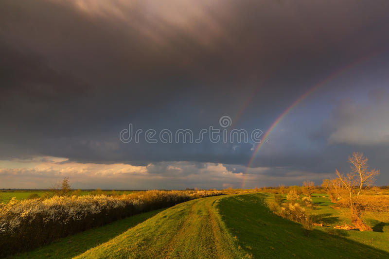 Ominous stormy sky over natural flooded river royalty free stock images