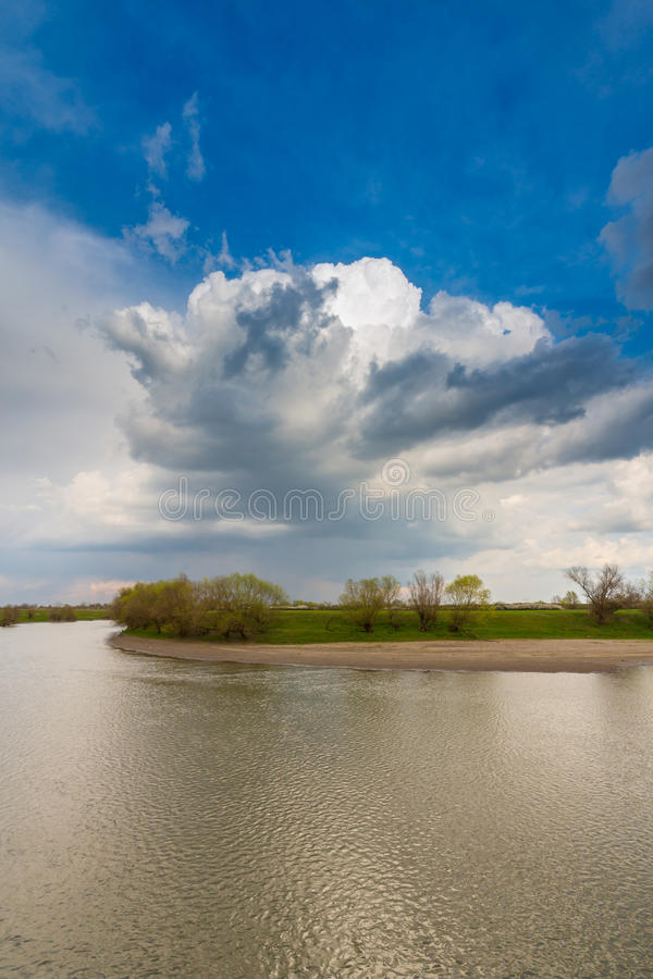 Ominous stormy sky over natural flooded river stock photo
