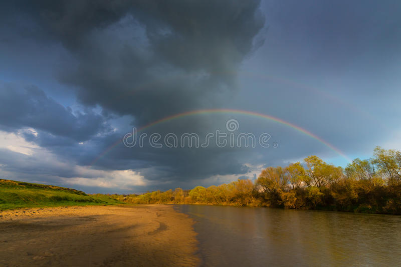 Ominous stormy sky over natural flooded river royalty free stock image