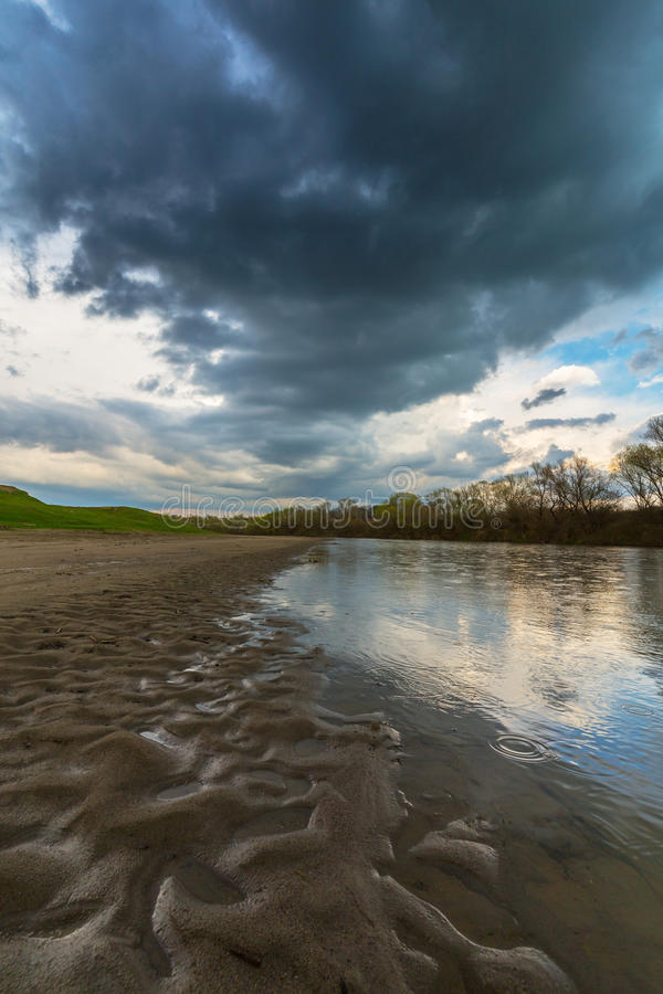 Ominous stormy sky over natural flooded river stock image