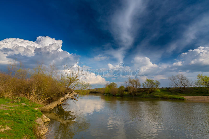 Ominous stormy sky over natural flooded river royalty free stock photography
