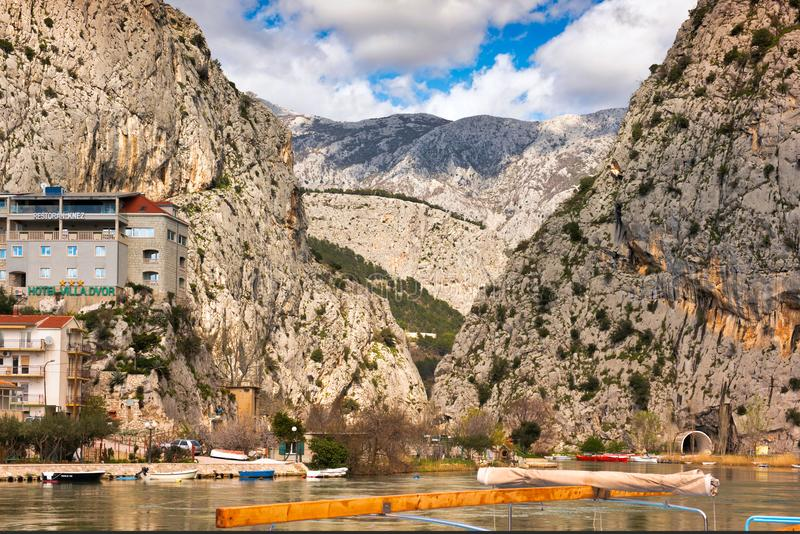 Omis Croatia karst mountains boats, houses & hotels. Jagged karst mountains with boats in the foreground, houses and hotels crowd the cliffs on the Croatian stock images