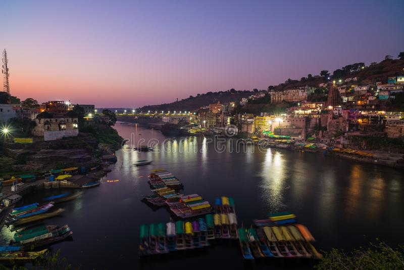 Omkareshwar cityscape at dusk, India, sacred hindu temple. Holy Narmada River, boats floating. Travel destination for tourists and royalty free stock photography