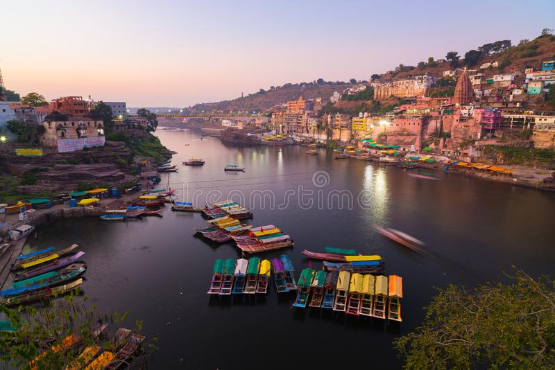 Omkareshwar cityscape at dusk, India, sacred hindu temple. Holy Narmada River, boats floating. Travel destination for tourists and royalty free stock photos