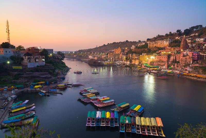Omkareshwar cityscape at dusk, India, sacred hindu temple. Holy Narmada River, boats floating. Travel destination for tourists and royalty free stock images