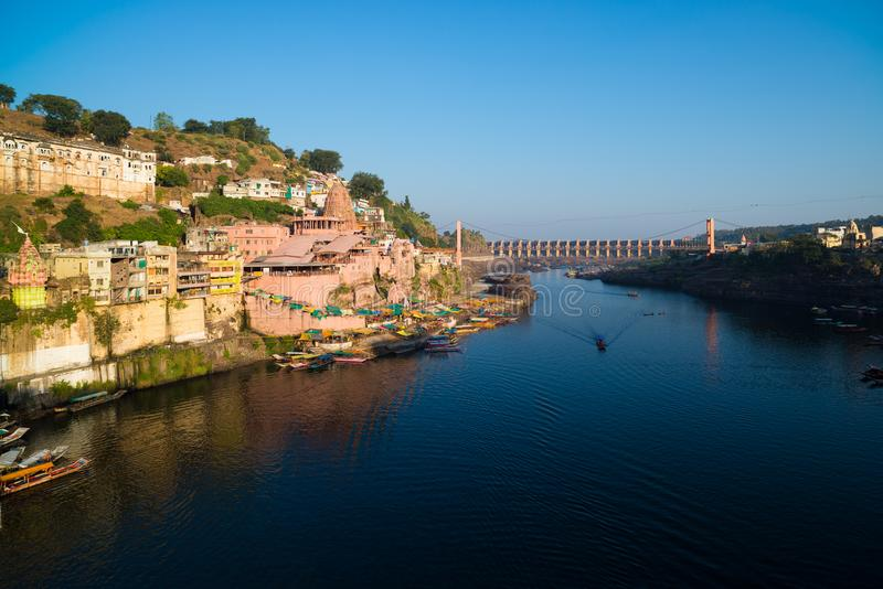 Omkareshwar cityscape, India, sacred hindu temple. Holy Narmada River, boats floating. Travel destination for tourists and pilgrim royalty free stock photography