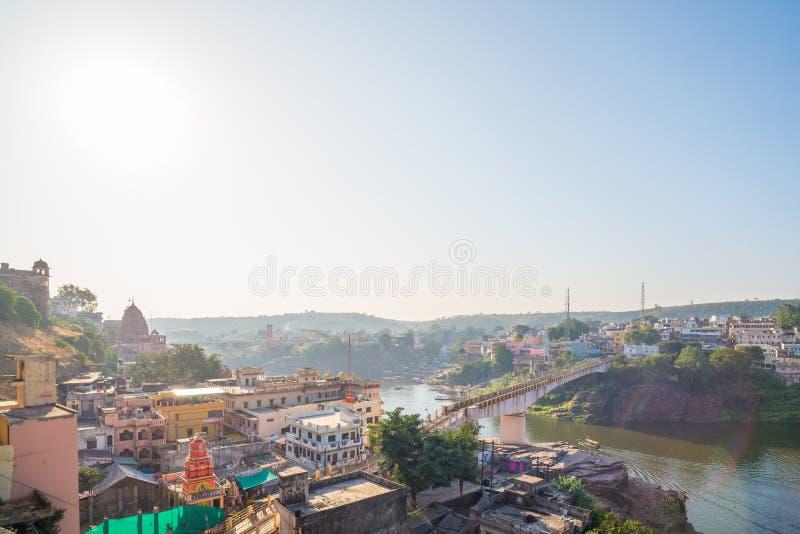 Omkareshwar cityscape, India, sacred hindu temple. Holy Narmada River, boats floating. Travel destination for tourists and pilgrim stock photo