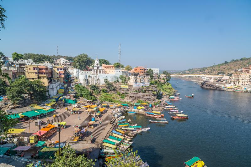 Omkareshwar cityscape, India, sacred hindu temple. Holy Narmada River, boats floating. Travel destination for tourists and pilgrim. S stock photo
