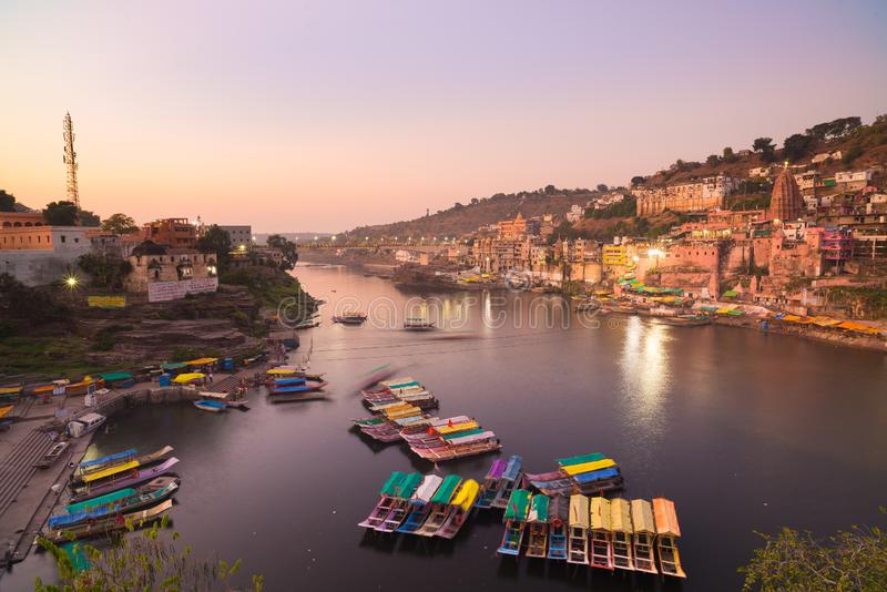 Omkareshwar cityscape, India, sacred hindu temple. Holy Narmada River, boats floating. Travel destination for tourists and pilgrim stock images