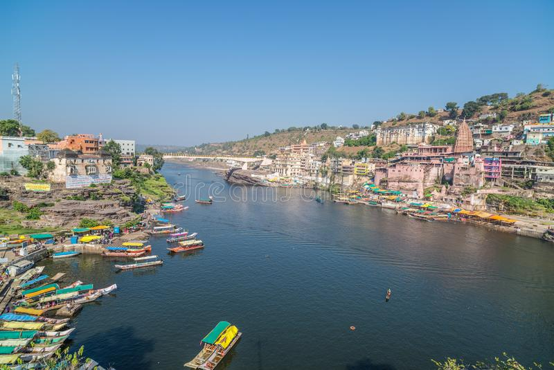 Omkareshwar cityscape, India, sacred hindu temple. Holy Narmada River, boats floating. Travel destination for tourists and pilgrim stock photo