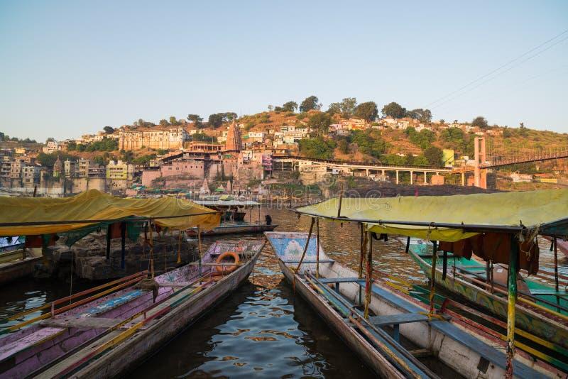Omkareshwar cityscape, India, sacred hindu temple. Holy Narmada River, boats floating. Travel destination for tourists and pilgrim royalty free stock image
