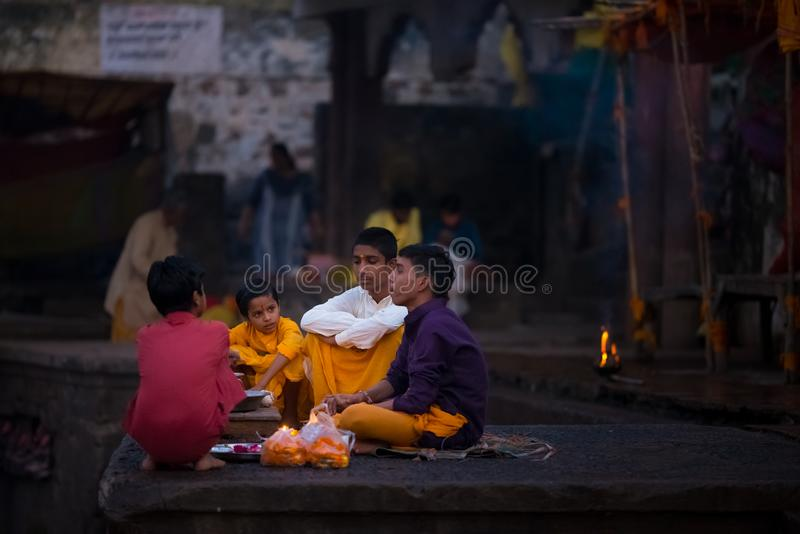 Young people attending religious ceremony on holy river at Omkareshwar, India, sacred town for Hindu religion. stock image