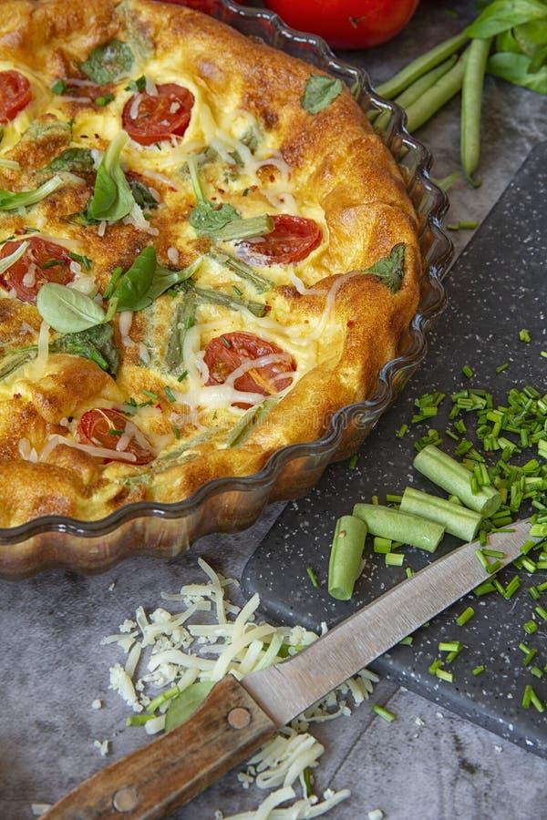 Omlet w piekarniku z fasolkami szparagowymi, pomidorami, ziele i serem, Jedzenie na ciemnym tle obrazy stock