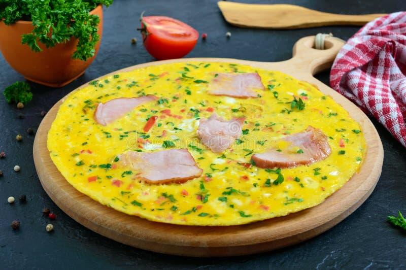 Omlet z baleronem, ser, zielenieje na drewnianej desce na czarnym tle Fritata - wy?mienicie, ?niadanie obraz stock