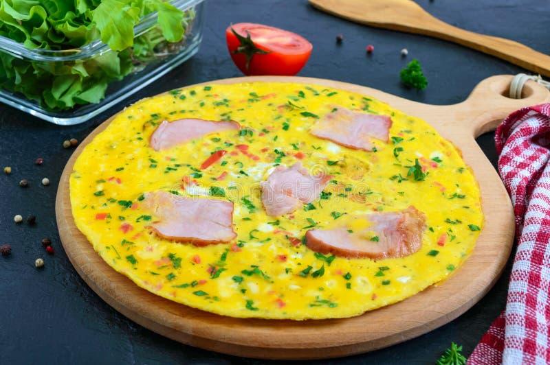 Omlet z baleronem, ser, zielenieje na drewnianej desce na czarnym tle Fritata - wy?mienicie, ?niadanie obrazy royalty free