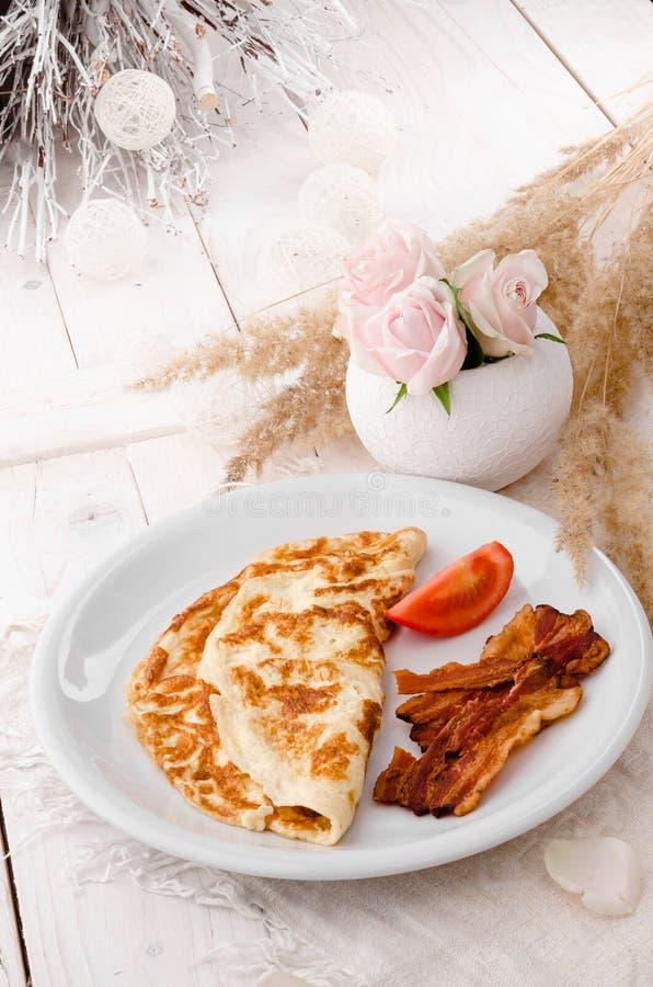 Omlet z crispy smażącymi pomidorami na bielu talerzu na drewnianym stole i bekonem, przegląda z góry zdjęcie royalty free