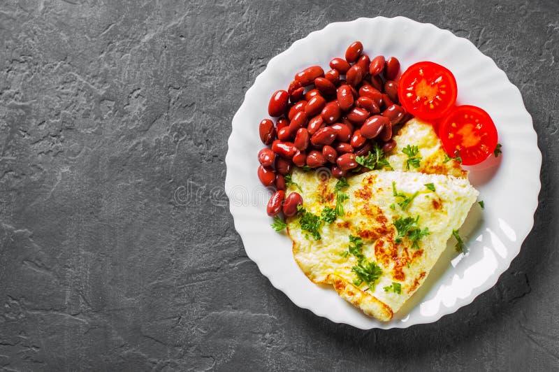 Omlet z czerwonymi fasolami i pomidorem w bielu talerzu na zmroku fotografia royalty free