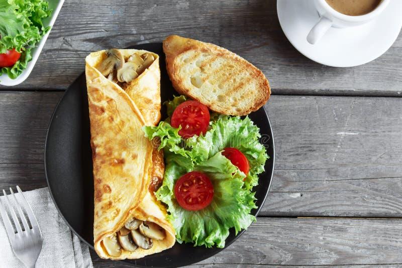 Omlet z pieczarkami dalej z sałatką i pomidorem zdjęcia royalty free