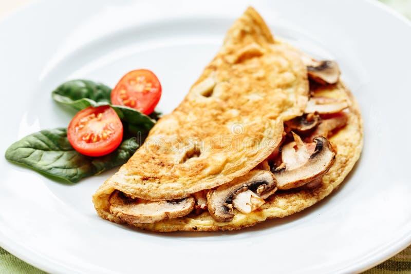 Omlet z pieczarkami słuzyć na bielu talerzu z czereśniowymi pomidorami i szpinakami zdjęcia royalty free