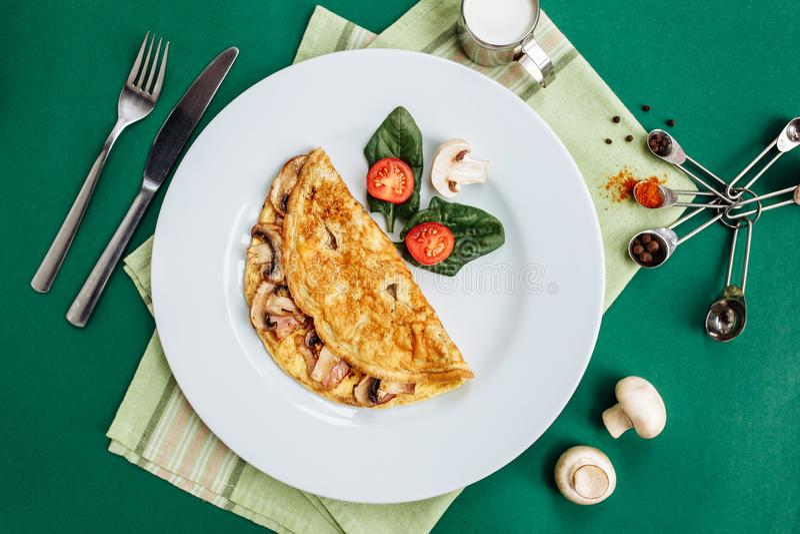 Omlet z pieczarkami słuzyć na bielu talerzu z czereśniowymi pomidorami i szpinakami zdjęcie royalty free