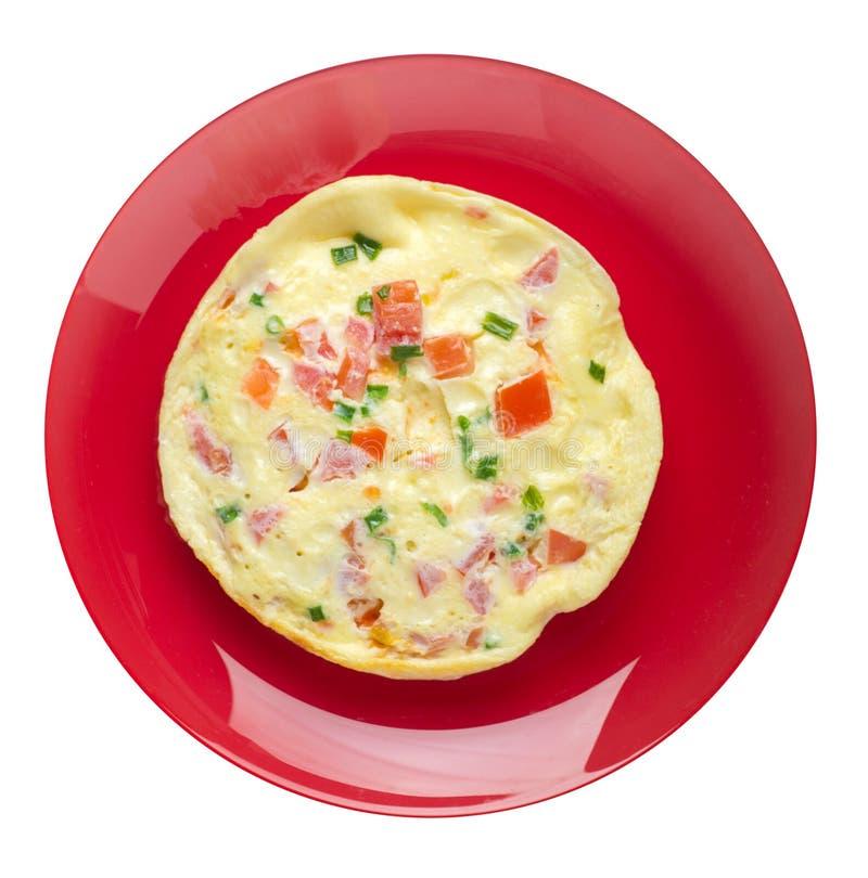 Omlet z pomidorami i zielonymi cebulami na talerzu odizolowywającym na białym tle omletu odgórny widok zdrowe ?niadanie obrazy stock