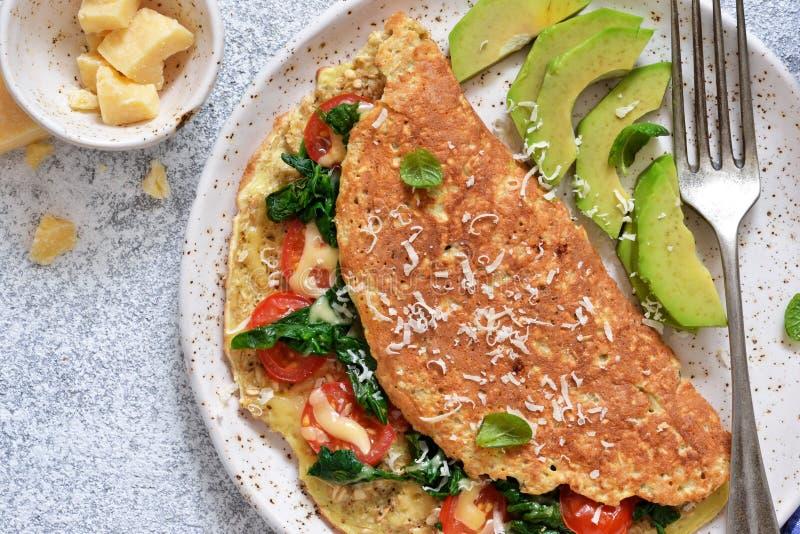 Omlet z pomidorami, serem i basilem w talerzu na kuchennym stole, na widok zdjęcia royalty free