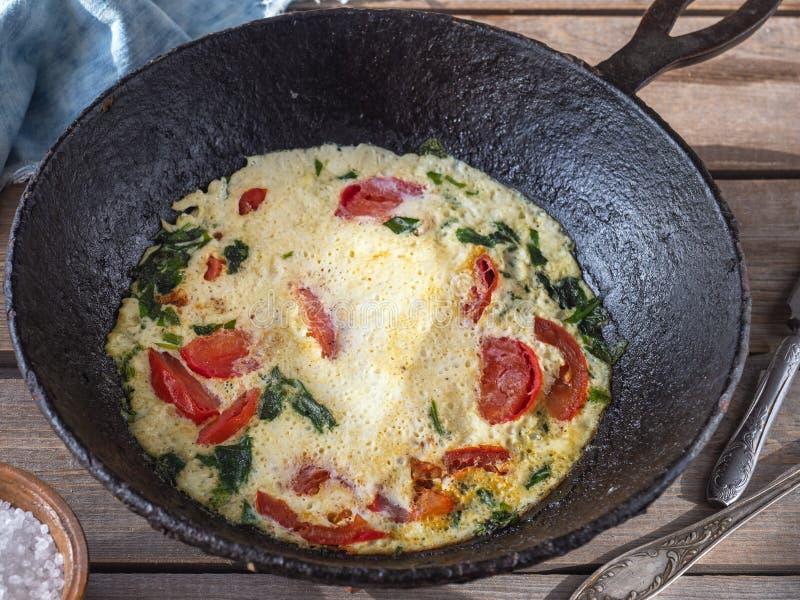 Omlet z pomidorami w round obsady żelaza niecce na starym deska stole, bawełnianych pieluchach i prostackiej soli w gliny soli, obraz royalty free