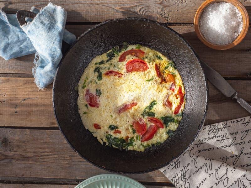 Omlet z pomidorami w round obsady żelaza niecce na starym deska stole, bawełnianych pieluchach i prostackiej soli w gliny soli, zdjęcia royalty free